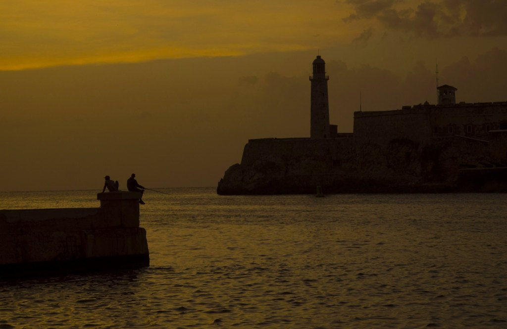 Силуэт крепости и двух рыбаков на закате на пирсе