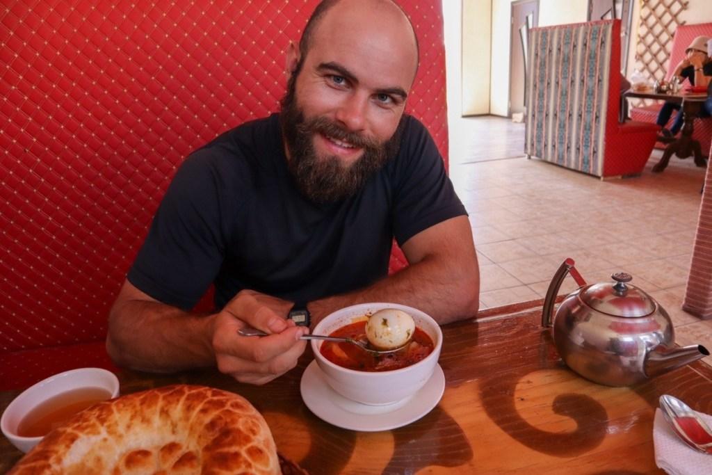 Мужчина ест суп с яйцом