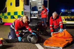 Emergency team assisting injured motorbike man driver at night