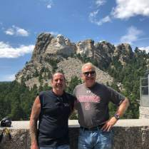 2 Men in front of Mount Rushmore