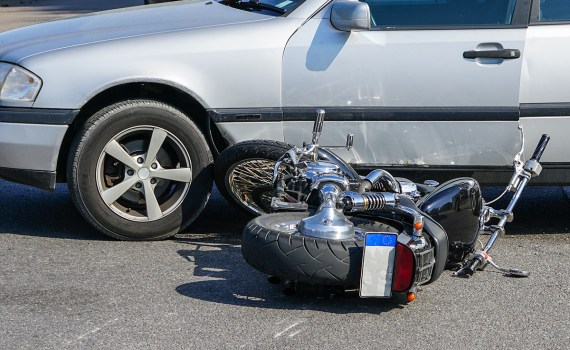 motorcycle collision with a car on city street