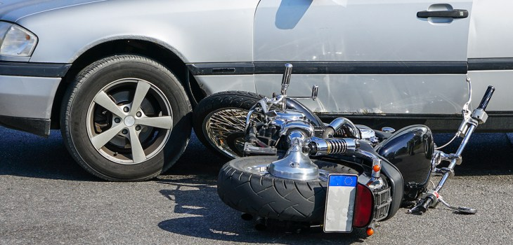 traffic accident, motorcycle collision with a car on city street, overturned motorcycle
