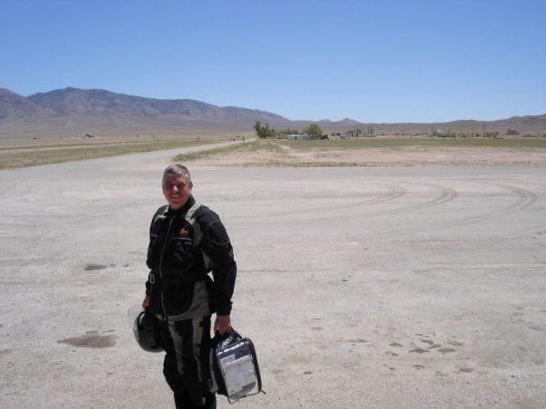 Motorradfahrer mit Helm und Tankrucksack bei einer Rast an der Area 51 in Rachel, NV (USA) bei 45° C,