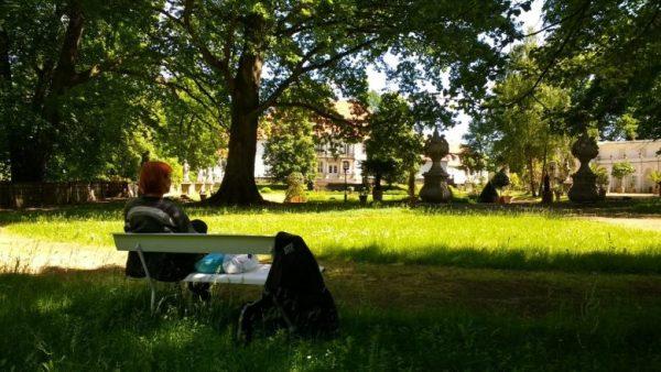 Einer der idyllischen Picknickplätze: Rothaarige Motorradfahrerin beim Picknick auf einer Bank im Schloßpark von Wiepersdorf in Brandenburg