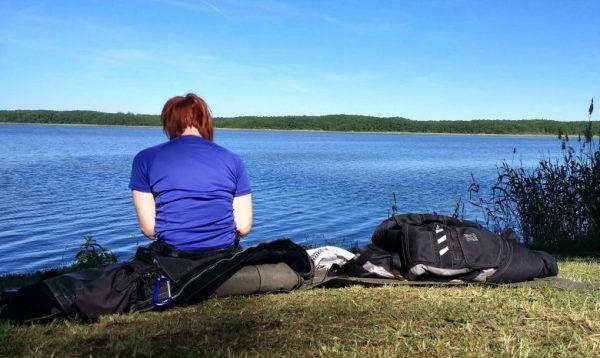 Rothaarige Motorradfahrerin mit blauem Hemd bei einem Picknick am Mellensee, Lkr. Teltow-Fläming in Brandenburg