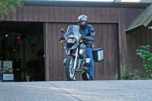 Motorradfahrer auf BMW R 1200 GS vor seiner Garage