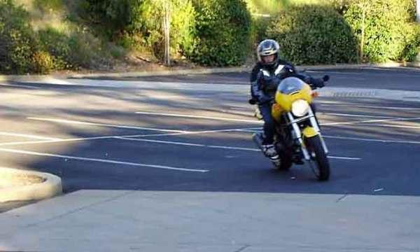 Motorradfahren mit Kindern: Junge auf einem gelben Motorrad Ducati Monster 750 bei Fahrschulübungen als Beispiel für Motorradfahren mit Kindern