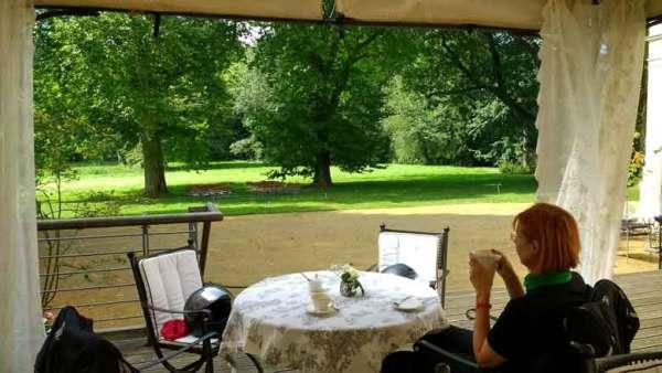 Rothaarige Motorradfahrerin auf der Terrasse des klassizistischen Schlosses Steinhöfel beim Kaffee trinken während einer Motorradtour Spree Oderland