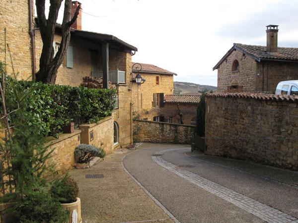 Dorfstrasse im Beaujolais mit Häusern aus goldenen Steinen, befahren bei einer winterlichen Beaujolais Motorradtour