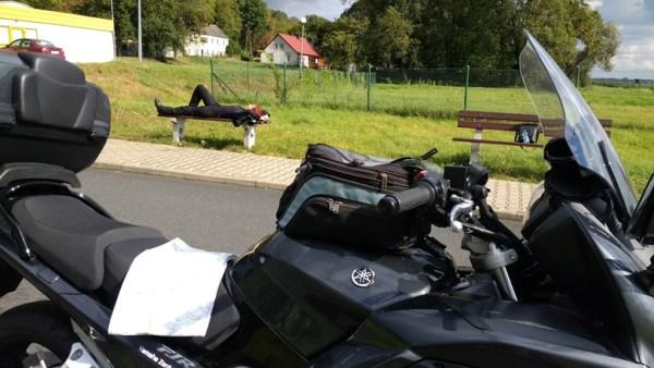 Rothaarige Motorradfahrerin auf einer Bank liegend mit einem Motorrad im Vordergrund bei einer Ruhepause an der Fähre Gozdowice an der Oder