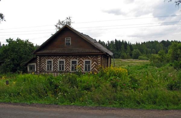 Russisches Holzhaus mit sparrenförmigen Verzierungen am Strassenrand und verwildertem Garten beim Motorradfahren in Moskau und der Provinz