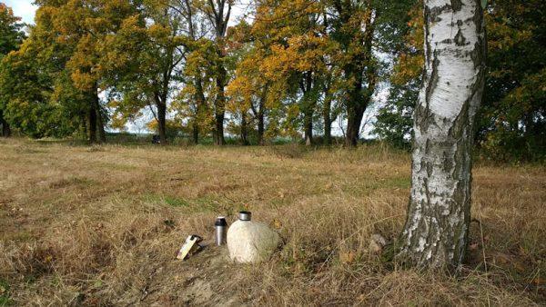 Thermosflasche mit Picknick und einem Feldstein auf dem Schlachtfeld von Zorndorf (Sarbinowo) aus dem Siebenjährigen Krieg