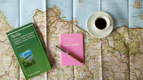 Notizbuch, italienischer Reiseführer und eine Tasse Espresso auf einer Landkarte von Sizilien als klassische Ergänzung zu den Smartphone-Apps für Motorradtouren