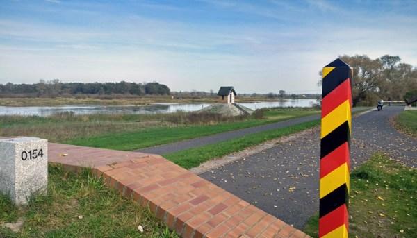 Oder-Neisse-Grenze mit einem schwarz-rot-goldenen Grenzpfahl im Vordergrund und einem Pegelhäuschen am Ufer der Oder