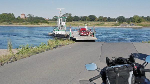Bild von der Faehre Sandau ueber die Elbe mit einer Yamaha FJR 1300 und der Laurentius/Nikolaus-Kirche am gegenueberliegenden Flussufer bei einer Romanik Motorradtour