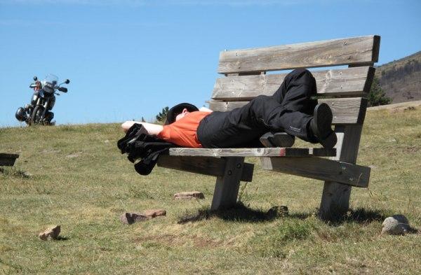 Tips für Solo Motorradfahrer: Ruhepausen einlegen. Motorradfahrerin auf Ruhebank