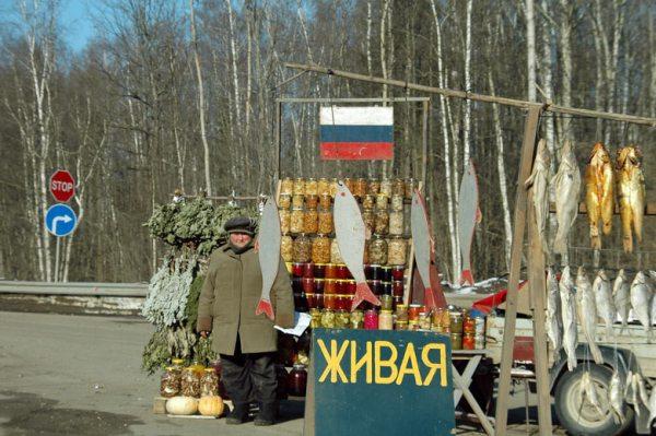 Tips für Solo Motorradfahrer: Warm anziehen. Verkäuferin vor einem Fischverkaufsstand an einer russischen Landstraße im Winter mit getrockneten Fischen