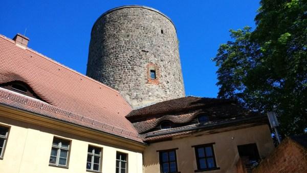Bild vom Bergfried der Burg Rabenstein mit zwei Flügelgebäuden im Landkreis Potsdam-Mittelmark in Brandenburg