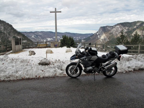 Resistance-Gedenkstätte mit einer BMW R 1200 GS und einem hohen Kreuz im Vordergrund vor einer kahlen Bergkette bei einer Motorradtour durch den winterlichen Vervors