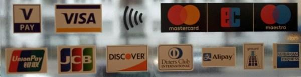Bild mit den Logos von Kreditkarten an der Glastür eines Geschäfts