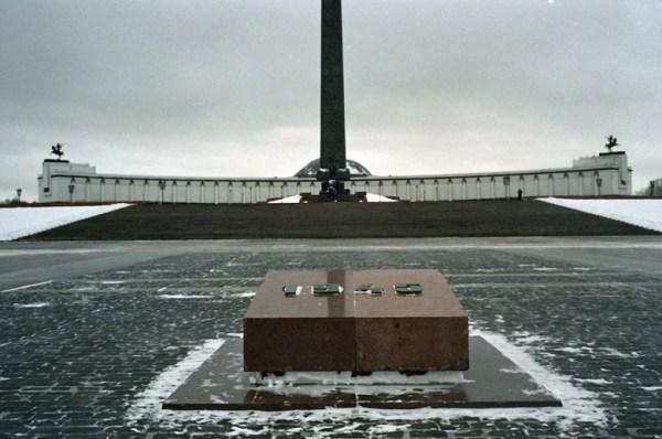 Siegesplatz auf dem Poklonnaja Hügel in Moskau im Winter mit der Siegeshalle im Hintergrund und einem Gedenkstein aus rotem Granit mit der Jahreszahl 1945