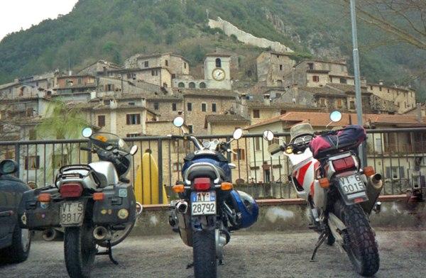 Drei Motorräder nebeneinander auf einem Parkplatz mit einem italienischen Bergdorf im Hintergrund bei einer Motorradtour durch Umbrien