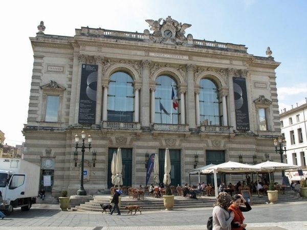 Theater von Montpellier im Bild mit einem Straßencafé und spazieren gehenden Menschen davor