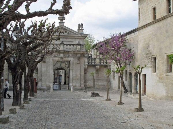 Eingang zur Kartause von Villeneuve mit lila blühenden Bäumen und einem barocken Eingangstor