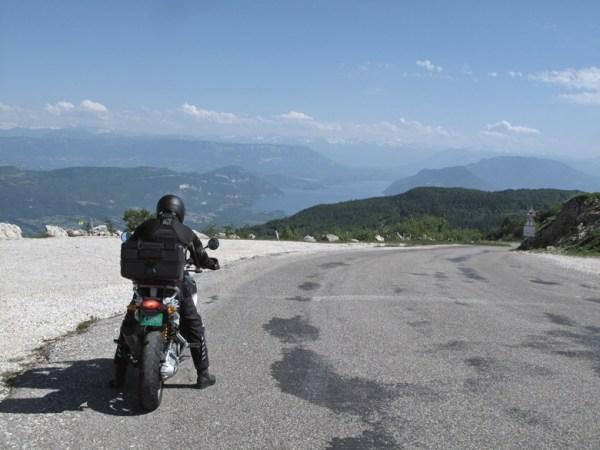 Panoramablick vom Col du Grand Colombier im Bugey aus auf den Lac de Bourget mit einem Motorradfahrer auf einer BMW R 1200 GS im Vordergrund, besucht bei einer Motorradtour zu Kraftorten am Grand Colombier