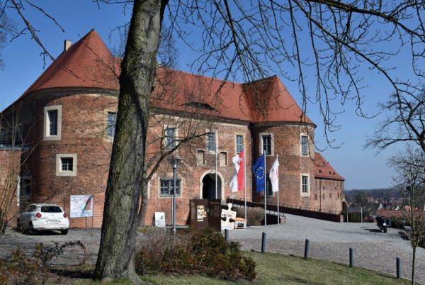 Motorradtour Hoher Fläming: Burg Eisenhardt in Bad Belzig in Brandenburg mit einem Motorrad vor dem Burgtor