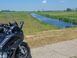 Bild von einem Kanal im Naturschutzgebiet bei Gülpe mit einem schwarzgrauen Motorrad Yamaha FJR 1300 im Vordergrund bei einer Motorrad-Hausrunde im Abseits