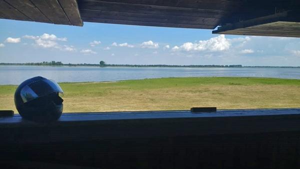 Blick auf das Vogelschutzgebiet Gülper See von einem Beobachtungsturm aus mit einem Motorradhelm im Vordergrund