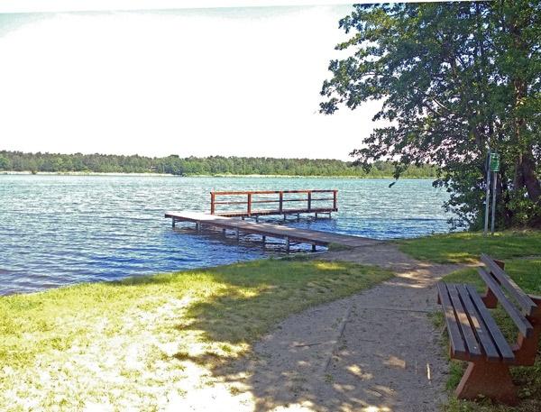 Köthener See bei einer Motorradtour durch Spreewald und Tagebaue mit einem Bootssteg und einer Ruhebank am Strand