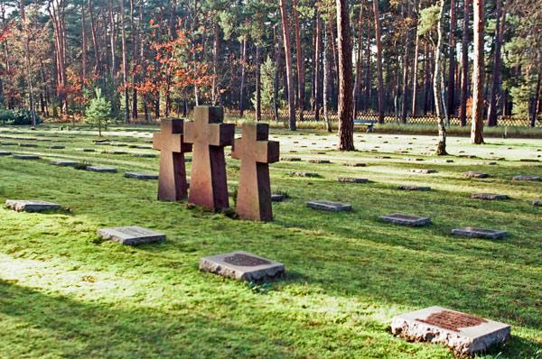 Waldfriedhof Halbe bei Berlin mit drei steinernen Gedenkkreuzen und mehreren Reihen von Kriegsgräbern