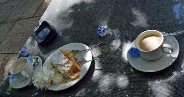 Teller mit hausgemachtem Apfelstrudel mit Sahne, zwei Fassen Kaffee und einem TomTom Urban Rider Navigationsgerät für Motorräder