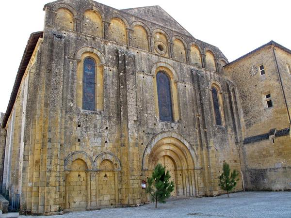Zisterzienserabtei Cadouin (Dordogne) aus gelbgrauem Sandstein mit zwei Kiefern neben dem Hauptportal, besucht bei einer Motorradtour Südwestfrankreich Teil 1