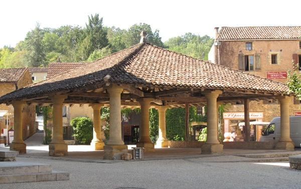 Markthalle in Cadouin (Dordogne), einem auf neun Säulen gestützten offenen Bau mit Ziegeldach und den umgebenden Häusern am Marktplatz