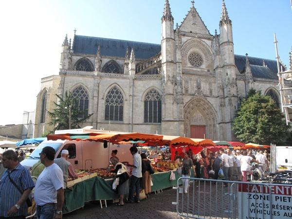 Markttreiben vor der Kathedrale von Bordeaux mit Verkaufsständen, orange Sonnenschirmen, Lieferwagen und Kunden, die sich die Waren anschauen