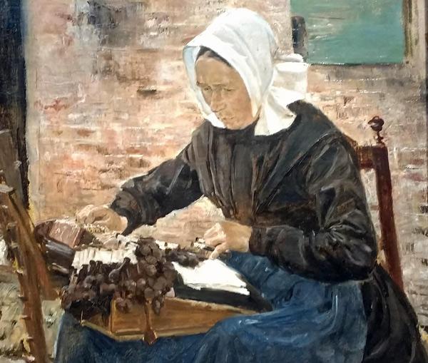 Klöpplerin mit weisser Haube, schwarzer Bluse und blauer Schürze bei der Arbeit auf einem Stuhl sitzend mit ihrem Werkstück auf den Knien
