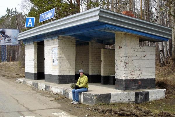 Bushaltestelle in Talzy, Irkutskaja Oblast' in Russland mit einer Frau auf einem Betonsockel sitzend