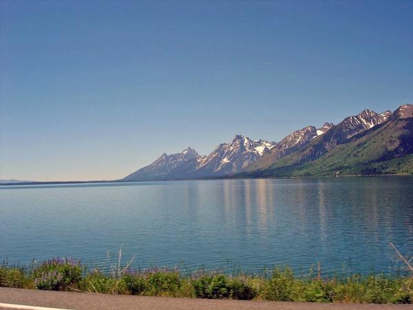 Jackson Lake Wyoming mit den Grand Tetons im Hintergrund, vom fahrenden Motorrad aus aufgenommen