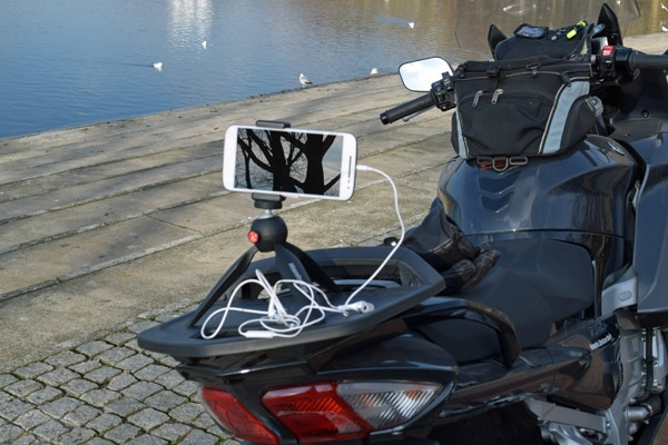 Mobiltelefon auf Ministativ mit Drahtauslöser auf dem Gepäckträger eines Motorrades als Teil der Fotoausrüstung für die Motorradtour