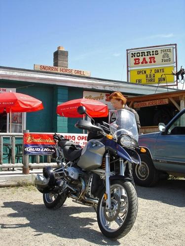 Motorrad BMW R 1200 GS mit einer rothaarigen Motorradfahrerin vor der Snorrin' Horse Bar in Norris, MT