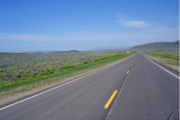 U.S. Route 89 Montana in weiter flacher Landschaft mit Bergen am Horizont