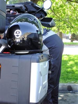 Motorradfahrerin über ihre Maschine gebeugt bei einer Motorradtour durch die Rocky Mountains auf der Utah State Route 24 bei einer Pause