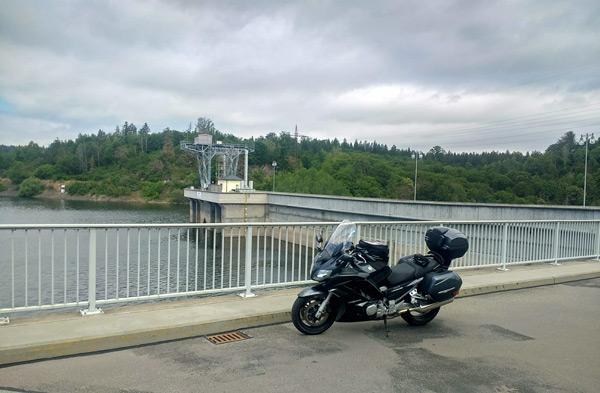 Damm der Bleilochtalsperre in Thüringen mit einem scharzen Motorrad Yamaha FJR 1300 bei einer Motorradtour durch den Thüringer Wald