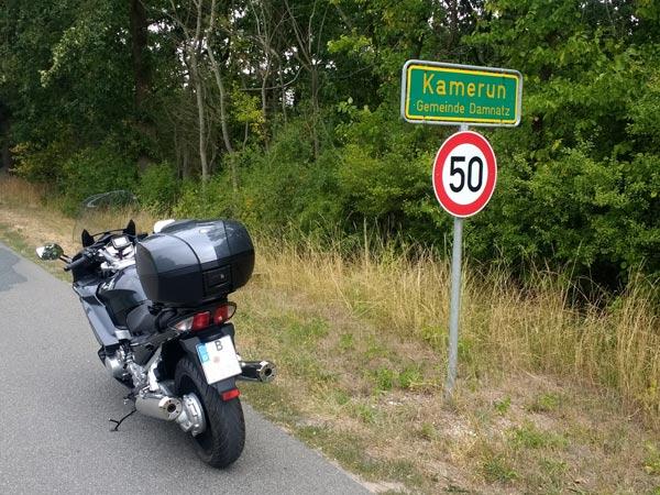 Motorrad vor dem Ortsschild Kamerun in Niedersachsen