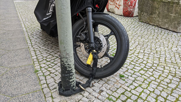 Motorrad, mit einer dicken Kette an einem Laternenmast befestigt, verhindert Motorraddiebstahl