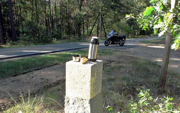 motorrad am kilometerstein mit thermosflasche