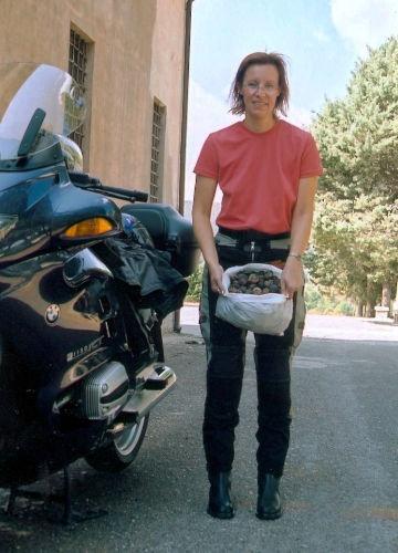 rothaarige motorradfahrerin mit einer tuete walnuesse und einer bmw r 1150rt bei einer motorradtour durch latium